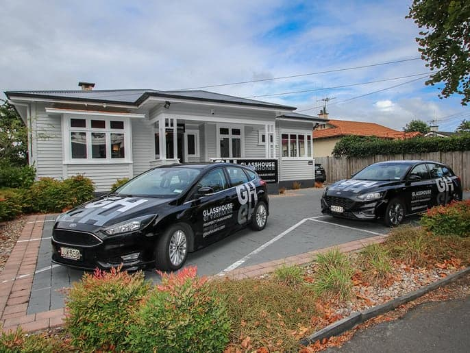 Glasshouse office front with branded cars