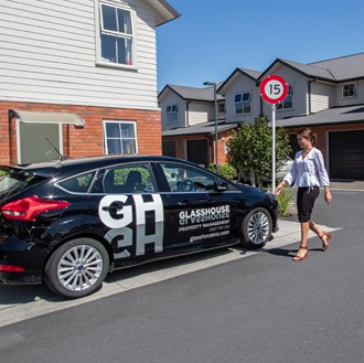 Hamilton property management agent walking to a car with Glasshouse written on it after completing a property inspection.