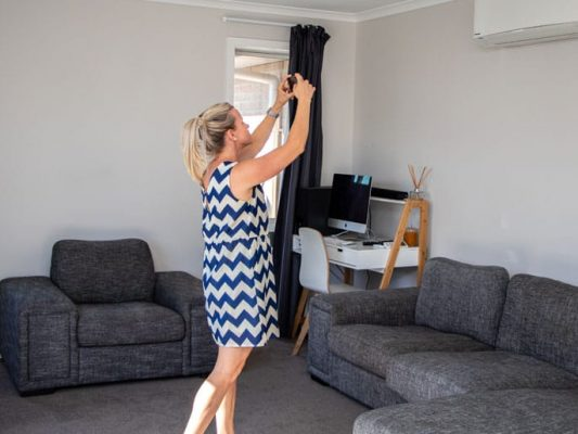 Woman in blue and white dress taking photos of a rental property as she completes a property management inspection.